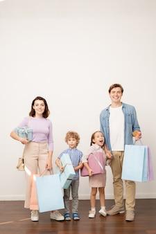 Glückliche junge eltern mit papiertüten und zwei kleine kinder mit geschenkboxen, die mit schwarzem freitagverkauf zufrieden schauen