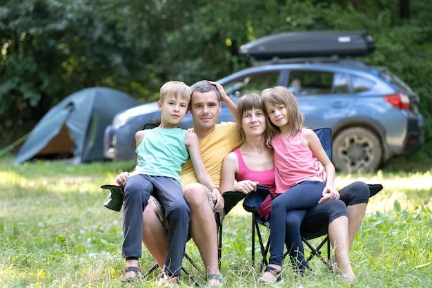 Glückliche junge eltern und ihre kinder, die im sommer zusammen auf campingplatz ruhen.