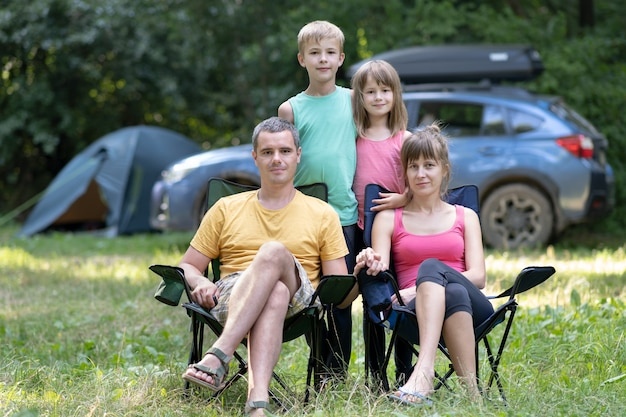 Glückliche junge eltern und ihre kinder, die im sommer zusammen auf campingplatz ruhen
