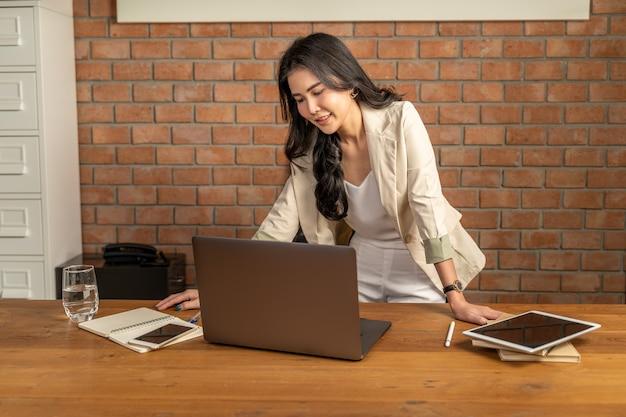 Glückliche junge erfolgreiche schöne asiatische geschäftsfrau, die ihren laptop-computer steht und betrachtet