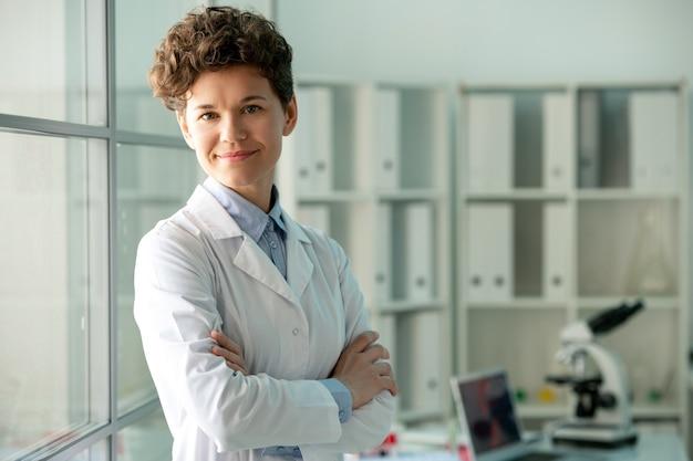 Glückliche junge erfolgreiche wissenschaftlerin oder forscherin im weißmantel, die gegen ihren arbeitsplatz im wissenschaftlichen labor steht