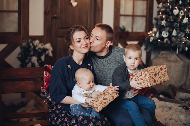 Glückliche junge erwachsene familie mit zwei jungen - kleinkind und baby, die eingewickelte weihnachtsgeschenke halten, die auf bank in gemütlichem raum mit geschmücktem weihnachtsbaum sitzen