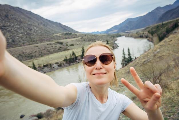 Glückliche junge erwachsene frau mit sonnenbrille und weißem t-shirt macht ein selfie und lacht in eine smartphone-kamera gegen die bergflusslandschaft. reisen, bloggen, aktiver lebensstil.