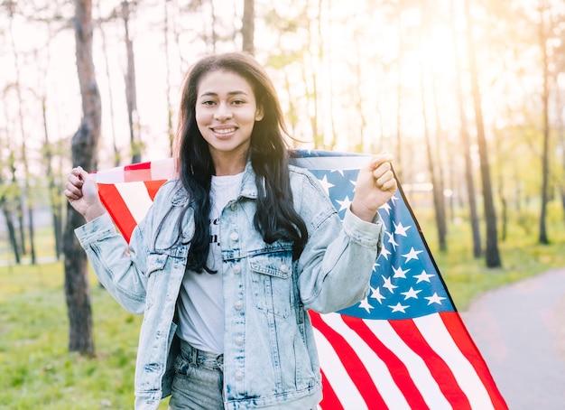 Glückliche junge ethnische frau mit amerikanischer flagge