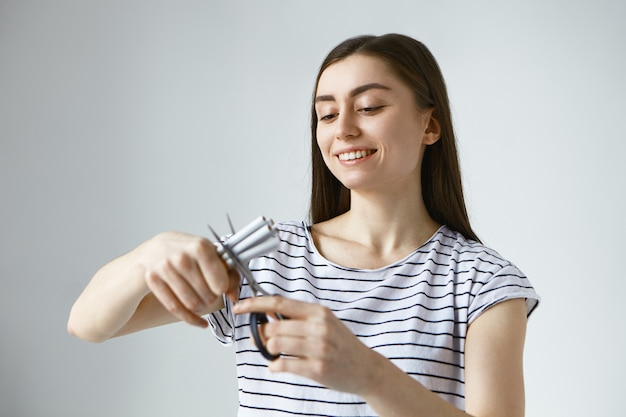 Glückliche junge europäische frau, die sich frei von zerstörerischer ungesunder tabakabhängigkeit fühlt, mehrere zigaretten hält und sie mit einer schere in zwei hälften schneidet