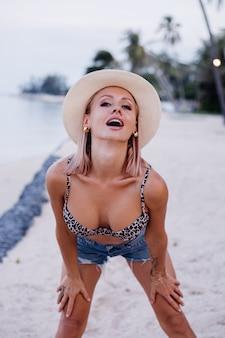 Glückliche junge europäische frau in leopardenspitzen-bikini-jeansshorts und klassischem weißem hut auf tropischem exotischem strand lächelnd posierend, das spaß spielerisches mädchen auf urlaubsreisekonzept hat