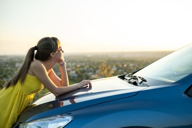 Glückliche junge fahrerin im gelben kleid, die einen warmen sommerabend neben ihrem auto genießt. reise- und urlaubskonzept.