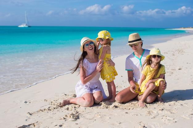 Glückliche junge familie auf weißem strand während der sommerferien