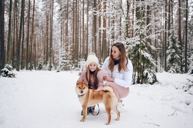 Glückliche junge familie der familie und kleines süßes mädchen in der rosa warmen oberbekleidung, die spaß mit rotem shiba-inu-hund im schneeweißen kalten kalten winterwald im freien geht