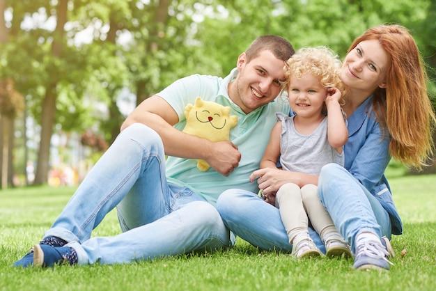 Glückliche junge familie, die am park sich entspannt