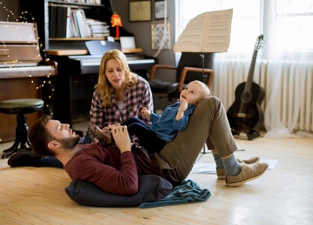 Glückliche junge familie, die auf dem boden am rustikalen raum spielt