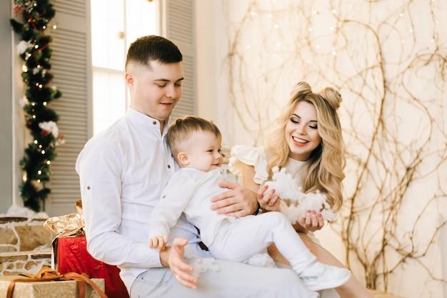 Glückliche junge familie, die auf der veranda des hauses sitzt, das für weihnachten geschmückt wird. lachen und sich auf den urlaub vorbereiten