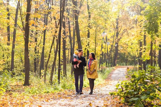 Glückliche junge familie, die die straße draußen in der grünen natur geht