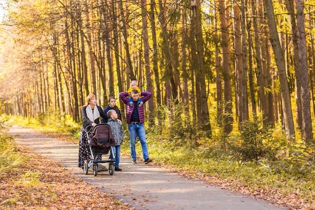 Glückliche junge familie, die die straße draußen in der herbstnatur geht