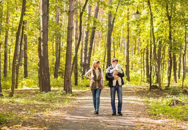 Glückliche junge familie, die die straße draußen in der herbstnatur geht Premium Fotos