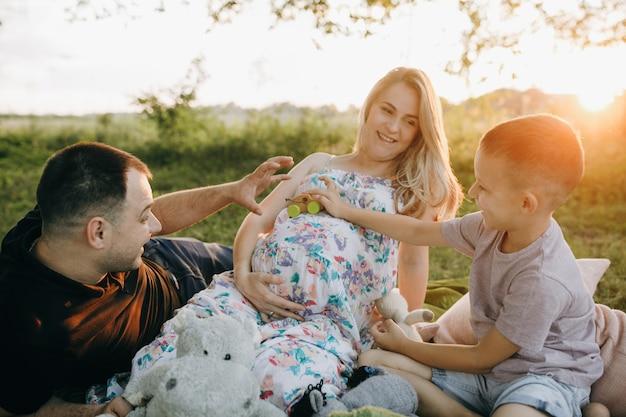 Glückliche junge familie, die im park ruht