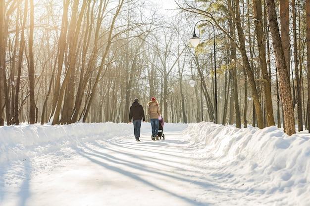 Glückliche junge familie, die im winter im park spazieren geht. die eltern tragen das baby im kinderwagen durch den schnee.