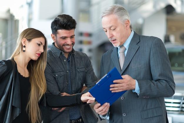 Glückliche junge familie, die mit dem verkäufer in einem autosalon spricht