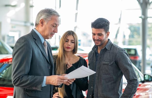 Glückliche junge familie, die mit dem verkäufer spricht und ihr neues auto in einem ausstellungsraum wählt