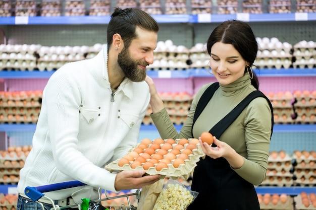 Glückliche junge familie, die nahe der theke mit eiern im supermarkt steht