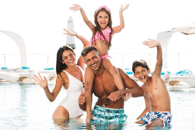 Glückliche junge familie, die spaß in einem schwimmbad hat