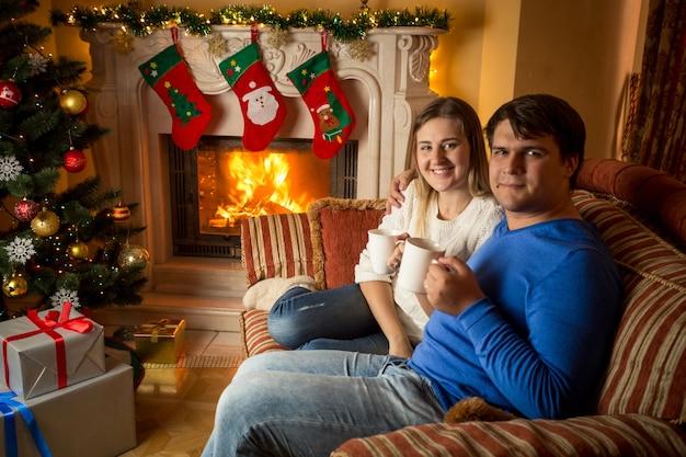 Glückliche junge familie, die tee auf dem sofa am kamin trinkt