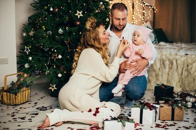 Glückliche junge familie, die weihnachten zusammen in ihrem gemütlichen haus feiern wird. urlaubskonzept