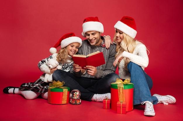 Glückliche junge familie, die weihnachtsmützen trägt, die lokal sitzen