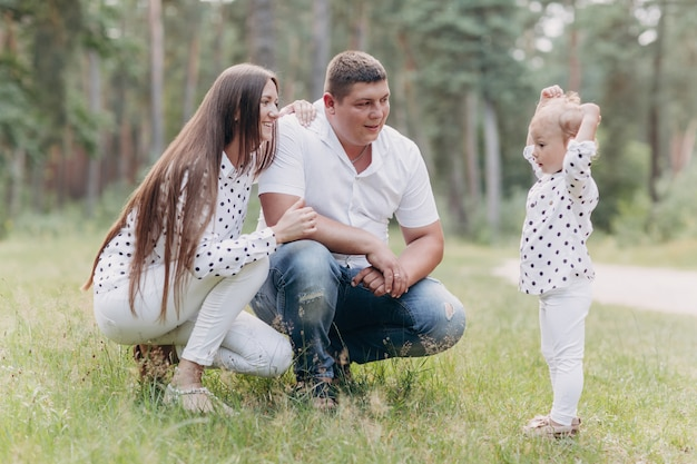 Glückliche junge familie, die zeit im freien an einem sommertag verbringt. mama, papa und kleine tochter im park. das konzept der sommerferien. muttertag, vatertag, babytag. zeit zusammen verbringen. familienlook