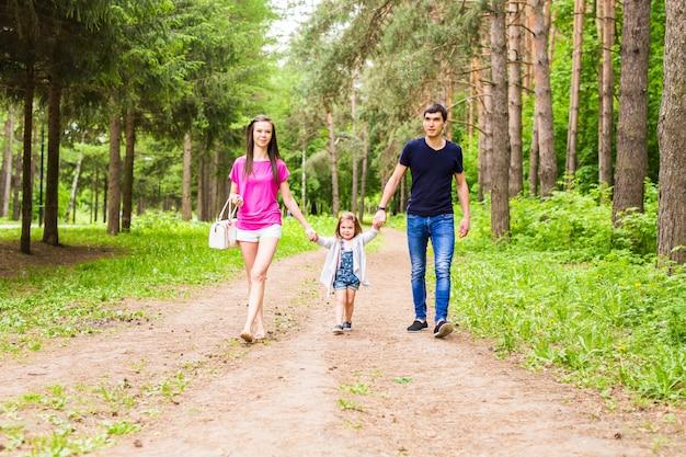 Glückliche junge familie, die zeit zusammen draußen in der grünen natur verbringt.
