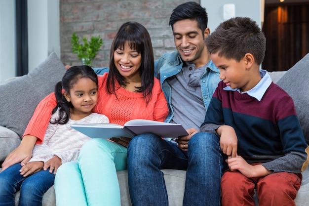 Glückliche junge familie, die zusammen ein buch liest