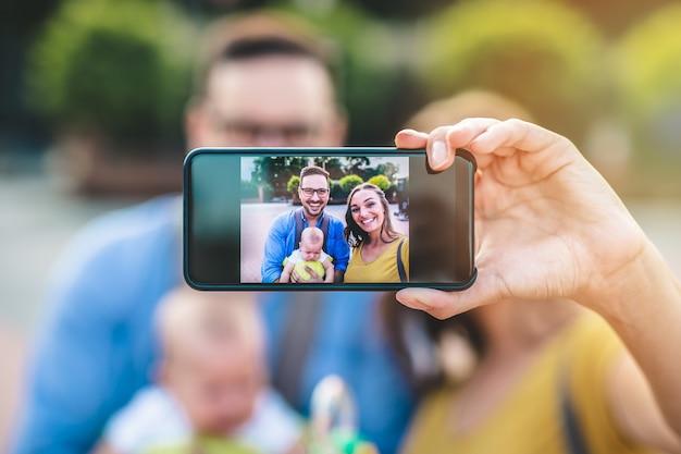 Glückliche junge familie, die zusammen genießt und selfie foto macht.