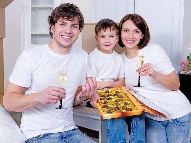 Glückliche junge familie, die zusammen neues zuhause feiert - drinnen