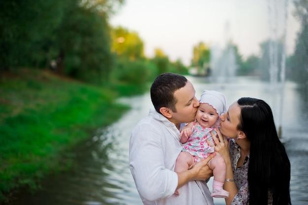 Glückliche junge familie, die zusammen zeit draußen in der grünen natur verbringt
