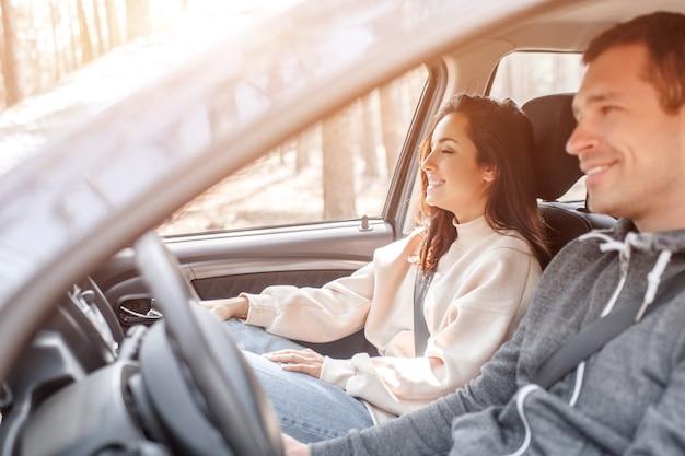 Glückliche junge familie fährt in einem auto im wald. ein mann fährt auto und seine frau sitzt in der nähe. reisen mit dem auto konzept.