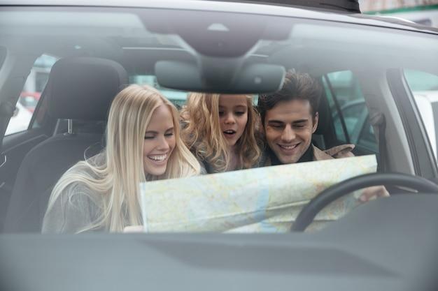 Glückliche junge familie im auto, das karte hält.