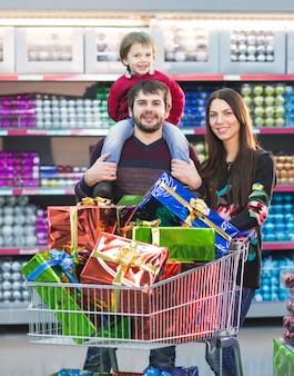 Glückliche junge familie im supermarkt wählt geschenke für christmass