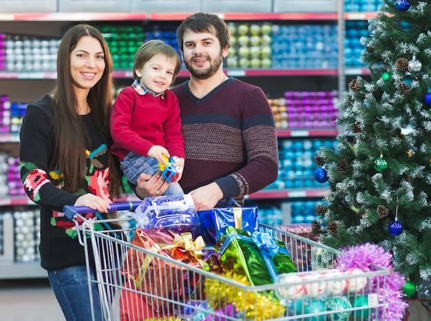 Glückliche junge familie im supermarkt wählt geschenke für das neue jahr.