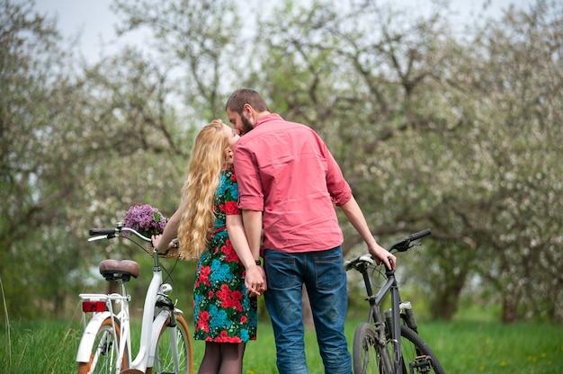 Glückliche junge familie in der liebe, die nahe den fahrrädern küsst