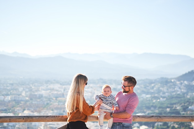 Glückliche junge familie mit dem kleinen netten jungen, der den sonnigen tag genießt