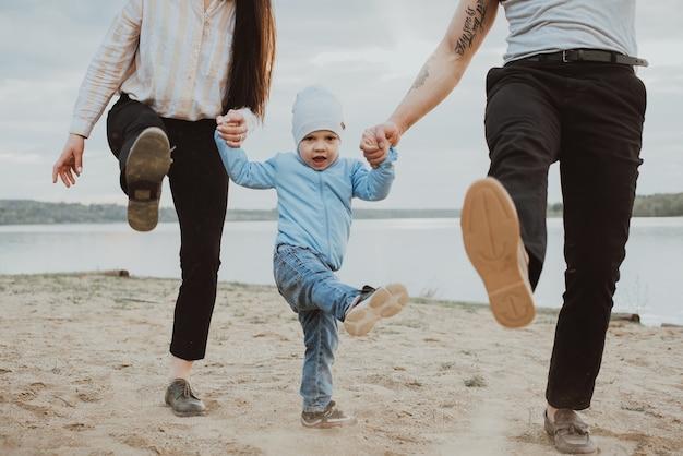 Glückliche junge familie mit dem kleinen sohn, der auf dem sand am strand im sommer spielt
