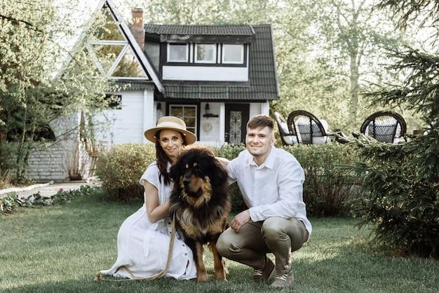 Glückliche junge familie mit einem hund auf einem haus, das mit einer hypothek gekauft wurde