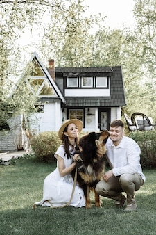 Glückliche junge familie mit einem hund auf einem neuen haus, das mit einer hypothek gekauft wurde