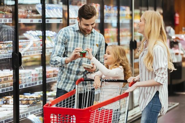 Glückliche junge familie mit einem kind, das mit einer laufkatze steht
