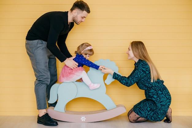 Glückliche junge familie mit einem kind, das spaß zusammen über gelber wand hat