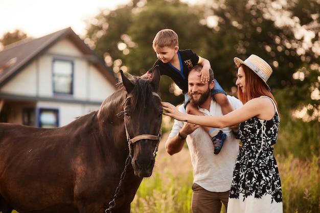 Glückliche junge familie mit einem kleinen sohn steht mit einem pferd vor einem kleinen landhaus