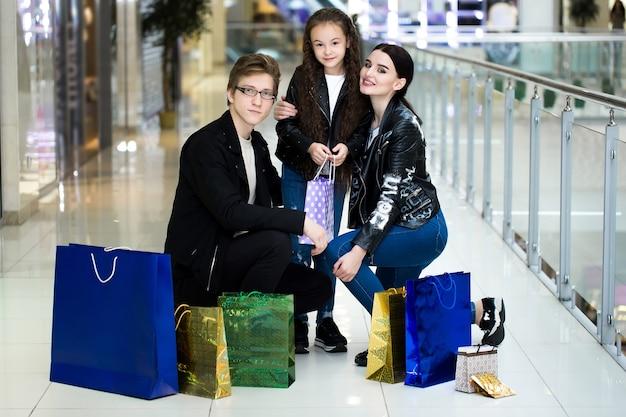 Glückliche junge familie mit papiertüten, die im einkaufszentrum einkaufen