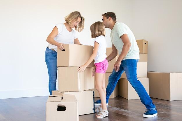 Glückliche junge familie mit pappkartons, die zu neuem haus oder zu wohnung ziehen