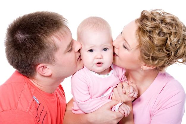 Glückliche junge familie mit schönem baby auf. eltern küssen das kind