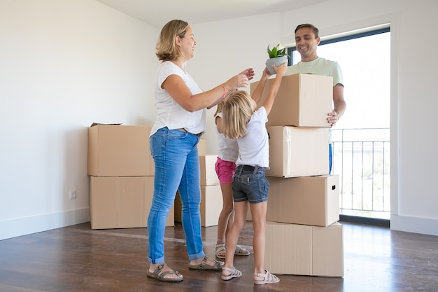 Glückliche junge familie mit umzugskartons in ihrem neuen haus